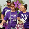 Carolyne Keith carries a colorful pinwheel with her mother's name during the Joplin Walk to End Alzheimer's on Saturday at Mercy Park. Keith lost her mother, Alma Lee Walker, to the disease in 2005.<br /> Globe | Laurie Sisk