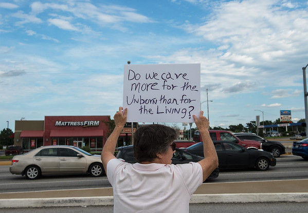 Dorothy Fulks, Webb City, holds a sign during a rally to stop the ongoing purge of eligible Missourians from the Medicaid program on Tuesday at 7th and Range Line Road.<br /> Globe | Roger Nomer