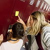 Katie Juergens helps a sixth grader with her locker combination on Thursday at North Middle School.<br /> Globe | Roger Nomer