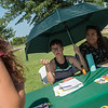 Maryana Roper, a Missouri Southern senior from Platt City, left, and Angelica Macias, a MSSU junior from Carthage, take shelter from the sun as they talk to students about joining the Spanish Club during Monday's first day of school picnic at MSSU.<br /> Globe | Roger Nomer