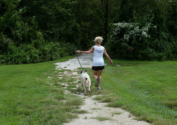 Kelly Johnson takes Riley for a run at the outdoor track at the Joplin Humane Society on Monday.<br /> Globe   Roger Nomer