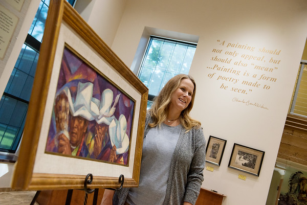 """Jennifer Walker, executive director of the NEO Development Foundation, talks about the Charles Banks Wilson painting """"White Hats"""" on Friday at NEO.<br /> Globe 