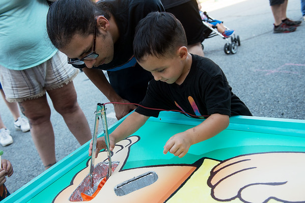 Armando Mendez and his son Lorenzo, 5, play a game of Operation at the Freeman Health System booth at Carl Junction's Second Tuesday event.<br /> Globe