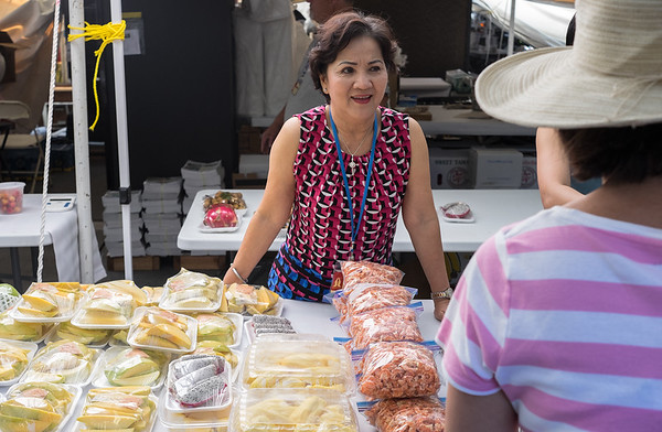 Vinh Nguyen, Port Arthur, Texas, talks with a customer at Marian Days at the Congregation of the Mother of the Redeemer on Wednesday.<br /> Globe | Roger Nomer