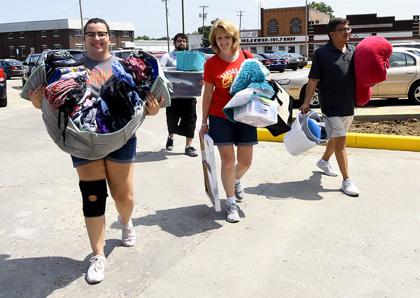 From the left: Olathe junior Allison Rangel gets helping hands from her brother, Justin Rangel, mother, Pam Rangel and father, David Rangel as she moves into the Opera House in the Block22 project in downtown Pittsburg on Saturday.<br /> Globe | Laurie Sisk