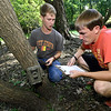 "Pittsburg State students Caleb Durbin, left and Brady Taylor install one of several ""camera traps"" on Thursday in a wooded area near Pittsburg. The two are part of a 50-state Smithsonian snapshot program intended to identify which specific mammals live in what areas.<br /> Globe 