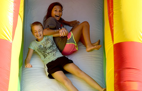 From the left: Cousins Hailey Hughes, 11, of Joplin and Addyson Hughes, 11, of Carl Junction enjoy a tandem slide down one of the inflatables on Wednesday night at Carl Junction First Assembly of God's Back to School Bash. The free event also included games, food and more.<br /> Globe | Laurie Sisk