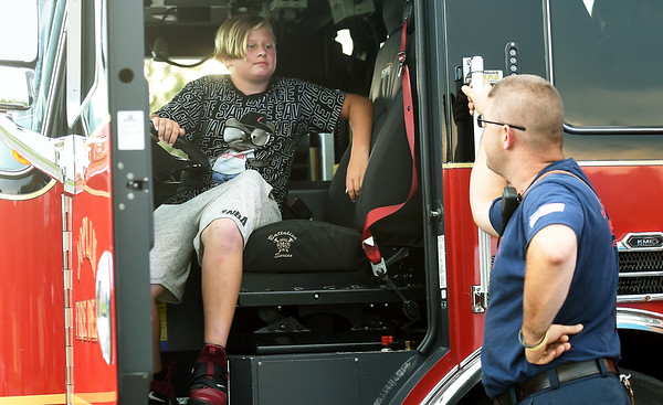Christian Rentfrow, 13, gets a closeup look at the inside of Engine No. 2 as he visits with Joplin Fire Department Driver/Engineer Christopher Johnson during the National Night Out on Tuesday at Schifferdecker Park. The event takes place annually in communities across the country and allows facilitates positive interaction between community members and local first responders.<br /> Globe | Laurie Sisk