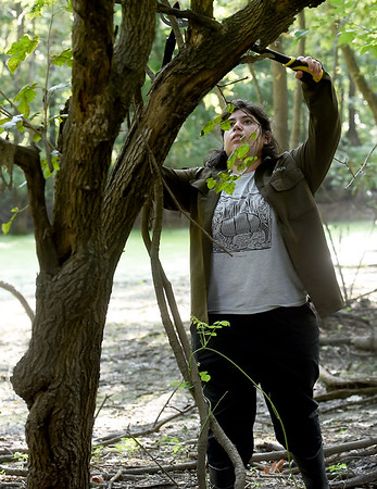 "Pittsburg State student Ximena Bogarin clears small obstructive limbs from a tree in preparation for the placement of  ""camera traps"" on Thursday in a wooded area near Pittsburg.<br /> Globe 