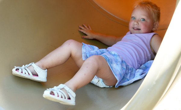 Two-year-old Vanessa Hughes enjoys a trip down a slide on Wednesday at Leonard Park.<br /> Globe | Laurie Sisk
