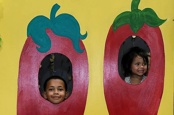 From the left: Zayder edwards, 9 and Zoey Zimmerman, 3, peer from behind a photo prop of peppers as they get into the pepper spirit during Pepper Fest on Saturday at the Empire Market. The event included kids activities, a salsa making contest and more.<br /> Globe | Laurie Sisk