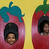 From the left: Zayder edwards, 9 and Zoey Zimmerman, 3, peer from behind a photo prop of peppers as they get into the pepper spirit during Pepper Fest on Saturday at the Empire Market. The event included kids activities, a salsa making contest and more.<br /> Globe   Laurie Sisk
