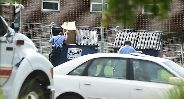 Members of the Springfield Fire Department Bomb Squad search a dumpster for a suspicious device on Thursday at the Royal Orleans Apartment Homes near Missouri Southern.<br /> Globe | Laurie Sisk