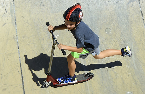 Nine-year-old Radley Baker smiles as he races around the bowl on his scooter on Wednesday at the Ewert Skate Park.<br /> Globe | Laurie Sisk
