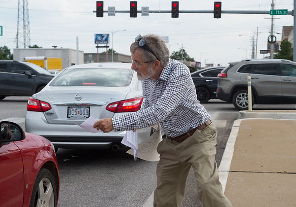 Elliott Denniston, Webb City, hands out information during a rally to stop the ongoing purge of eligible Missourians from the Medicaid program on Tuesday at 7th and Range Line Road.<br /> Globe   Roger Nomer