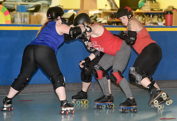 """From the left: Megan Tyler, aka """"Roc"""" tries to get past the blocking of Leray Caldwell, aka """"Ballz"""" and Hannah Whitney, aka """"Sugar Rush"""" as Melody McDannald, aka """"Mel Diablo"""" tries to score during practice for the Mo-Kan Roller Girlz on Thursday night at Spinning Wheels SK8 Center in Carl Junction.<br /> Globe 