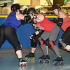 "From the left: Megan Tyler, aka ""Roc"" tries to get past the blocking of Leray Caldwell, aka ""Ballz"" and Hannah Whitney, aka ""Sugar Rush"" as Melody McDannald, aka ""Mel Diablo"" tries to score during practice for the Mo-Kan Roller Girlz on Thursday night at Spinning Wheels SK8 Center in Carl Junction.<br /> Globe 