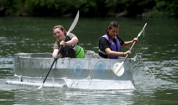 From the left: Sophia Schwartz, 15 and Nico Carlson, 14, compete in the Cardboard Canoe Race in their SS Salty Sisters canoe constructed by Girl Scout Troop 70391 on Saturday during the Shoal Creel Water Festival at Wildcat Glades.<br /> Globe | Laurie Sisk