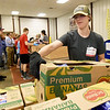 Missouri State University volunteer Meghann Robertson, of Iberia, helps package frozen meat last month at Ozarks Food Harvest in Springfield. Crews work on a tight time limit when handling the frozen foods.<br /> Globe | Laurie SIsk
