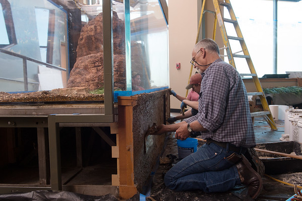 Terry Chase, with Chase Studio, works on the aquarium at the Shoal Creek Conservation Education Center on Thursday.<br /> Globe | Roger Nomer