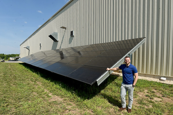 Ozarks Food Harvest Advocacy Coordinator Jordan Browning stands near one of several sets of solar panels last month on the Ozarks Food Harvest campus in Springfield. The panels provide about 20 percent of the warehouses' power.<br /> Globe | Laurie Sisk