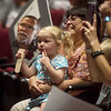 Lorin Curtis' granddaughter Elizabeth Ward, 7, and wife Tomoko Curtis, watch his speech with a cutout of his face during Monday's back-to-school rally at Joplin High School. Curtis was recognized as the Joplin teacher of the year.<br /> Globe | Roger Nomer