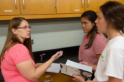 Dione Friel talks with Tiffany Pham, middle, and Nicole Sherwood, both sophomores at Carl Junction High School, about their lab notebooks on Thursday. Globe | Roger Nomer