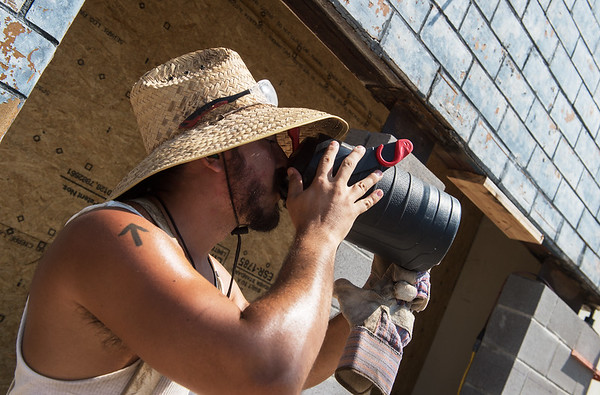 JD Dempster, with Kevin Harrison Masonry, takes a water break while working on a project on Main Street on Monday.<br /> Globe | Roger Nomer