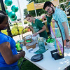 Amber Carr, assistant library director of Spiva Library, and Kaden Propps, a Missouri Southern junior from Purdy, watch as Darche Ntsomi, a MSSU international student from Congo, spins a prize wheel at the Spiva Library booth during Monday's back to school picnic at MSSU.<br /> Globe | Roger Nomer