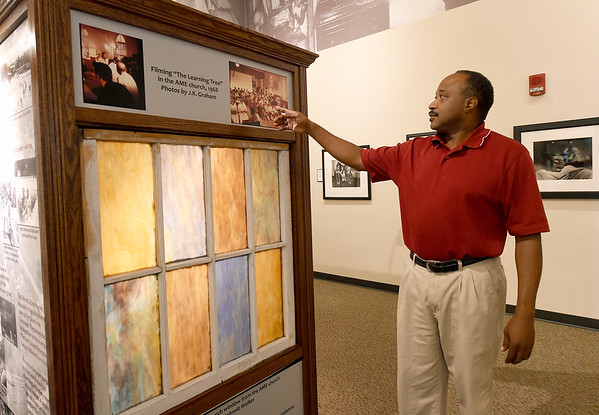 "Gordon Parks Museum's Executive Director Kirk Sharp stands near an exhibit of the old AME Church in Fort Scott, where scenes from Parks' ""The Learning Tree"" were filmed in 1968.<br /> Globe 