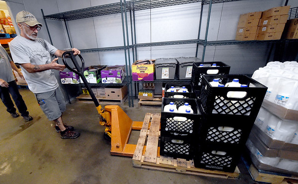 Crosslines warehouse manager Dan Ashton helps unload a pallet of milk from a Ozarks Food Harvest delivery last month at Crosslines. <br /> Globe | Laurie Sisk