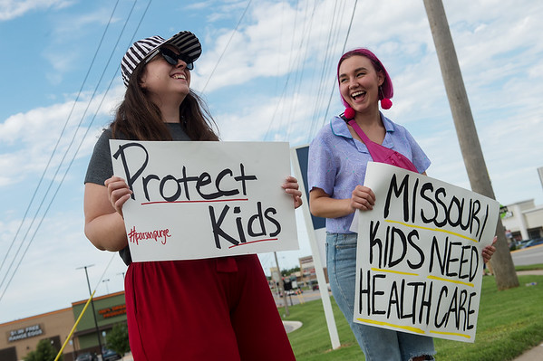 Johanna Wirthensohn and Sarah Robbins talk during a rally to stop the ongoing purge of eligible Missourians from the Medicaid program on Tuesday at 7th and Range Line Road.<br /> Globe | Roger Nomer