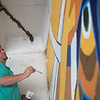 Burt Bucher eyes his handiwork as he paints on the mural near 6th and Virginia in downtown Joplin on Saturday.<br /> Globe | Roger Nomer