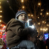 Globe/Roger Nomer<br /> Zachariah Gunlock, 3, keeps a sharp eye out for the start of the Christmas Parade atop his grandfather Randy Moss's shoulders in downtown Joplin on Tuesday.