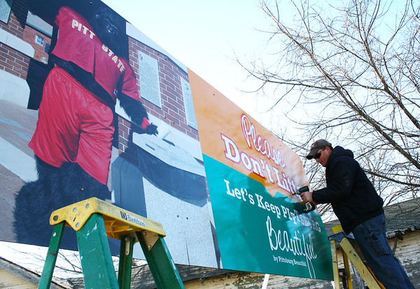 Globe/Andra Stefanoni <br /> Luke Warford, Jayhawk Signs of Pittsburg, installs one of two <br /> billboards Wednesday morning at the city limits of Pittsburg on East <br /> and West Fourth Street. The signs, sponsored by the volunteer <br /> organization Pittsburg Beautiful, are part of a city-wide campaign to <br /> clean up the community. Globe/Andra Stefanoni