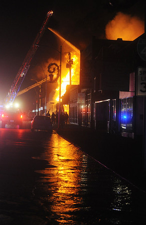 Globe/Roger Nomer<br /> Water pooling along Main Street reflects a fire at 16th and Main Streets on Tuesday evening.