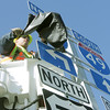 Globe/Roger Nomer<br /> Clay Novinger, with MODOT, unveils the new I-49 signs along Highway FF on Wednesday afternoon.