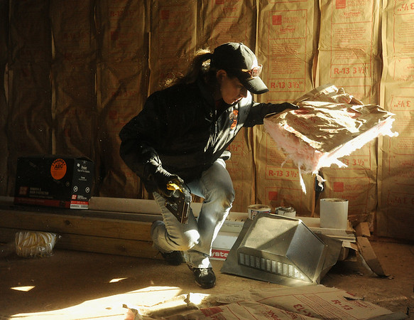 Globe/Roger Nomer<br /> Jaime Cope, with associate support at the Joplin Home Depot, works on insulation installation at a house on east 18th Street on Thursday morning.