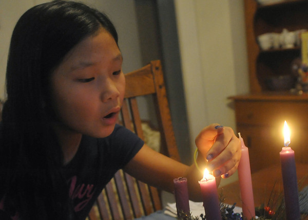 Globe/Roger Nomer<br /> Josie Franklin, 9, blows out an Advent candle on Wednesday afternoon.  The sisters take turns on who gets to blow out the candles from night to night.