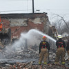 Globe/Roger Nomer<br /> A Joplin firefighter crew sprays down the wreckage of a building at 16th and Main on Wednesday afternoon.