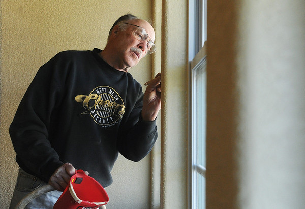 Globe/Roger Nomer<br /> Bob Davit, St. Louis, touches up paint on a window on a house on west 19th Street on Thursday morning.  This is Davit's fifth time in Joplin to volunteer.