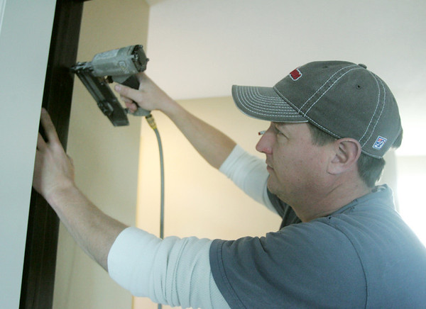 Globe/Roger Nomer<br /> Jack Hilbert, with Jack Hilbert Custom Trim, secures trim at a house on Pennsylvania on Tuesday afternoon.