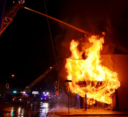 Globe/Joe Hadsall<br /> Fire engines douse a fire emerging from a building at 16th and Main Streets on Tuesday evening. The building housed Bucklin's Furniture and used to be a May's Drug Store.