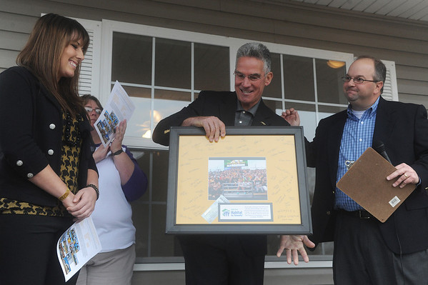 Globe/Roger Nomer<br /> Matt Lee, Joplin Area Habitat for Humanity board secretary, right, presents Mike Alden, University of Missouri Athletic Director, and Nicole Hudson, MU senior, with a signed photo to thank the university for its help with building houses in the Joplin area.