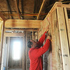 Globe/Roger Nomer<br /> Bryan Vowels, Joplin, staples insulation at a house on east 18th Street on Thursday morning.