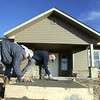 Globe/Roger Nomer<br /> Alfredo Urbina, left, and Ricardo Robles, with Maturino Concrete Construction, smooth the steps of a house at 2209 Pennsylvania on Tuesday afternoon.
