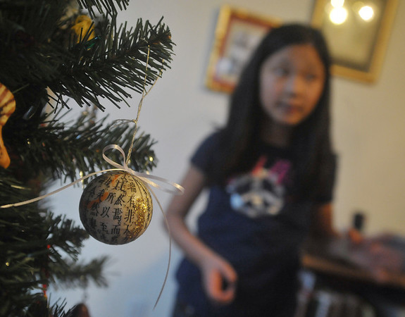Globe/Roger Nomer<br /> The Franklin family has a mix of Chinese and American Christmas ornaments on their tree during the holidays.