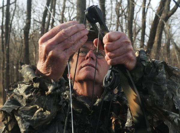 Globe/Roger Nomer<br /> Max Good attatches his bow to a line to transport it up to his tree blind in Parsons on Thursday.