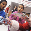 Globe/Roger Nomer<br /> Velysia Smith's, 6, eyes light up as she and her brothers Hunter, 5, center, and Sunshine, 4, receive presents from Santa at the Salvation Army Christmas lunch on Wednesday morning.