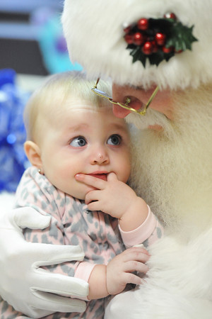 Nine-month-old Adelyn Carolus of Joplin looks up at Father Christmas as he holds her in the pediatric unit at Freeman West in Joplin on Monday afternoon, Dec. 23, 2013.<br /> Globe | T. Rob Brown